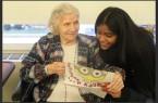 Rasheeda Ramsingh reading a holiday card with a woman in a senior home.  Photo Credit: Fawzia Rahman