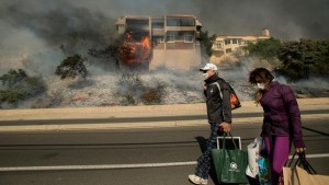 Family carries remaining belongings after escaping fire. Photo Credit: ABC 7 News