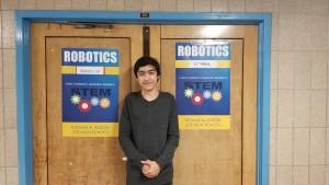 Caption: Jonathan Ustaev, standing in front of his favorite class; Robotics Photo Credit: Rickcarl Paningsoro
